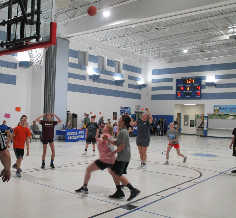 Basketball game with the ball high in the air.
