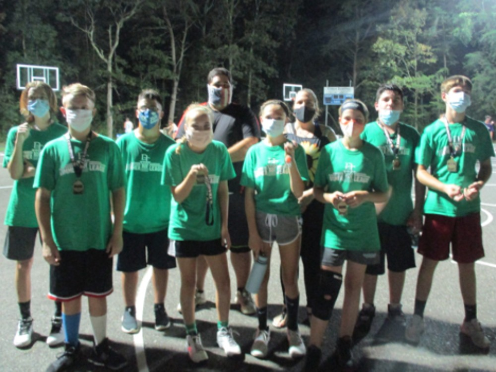 Basketball team in dark green posing for picture