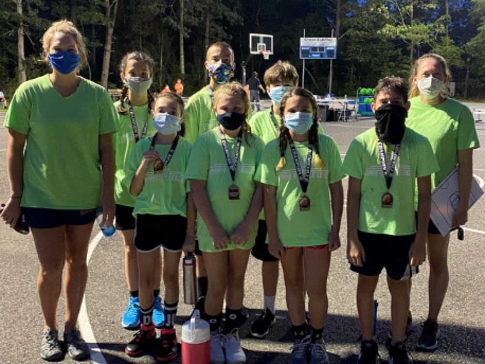Basketball team in green posing for picture